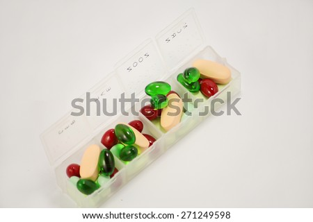 Colored pills, tablets and soft gel capsules in pill box on a white background - stock photo
