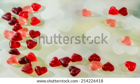 Colored (pink, red and orange), transparent heart shape jellies, hearts light background. - stock photo