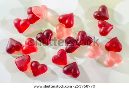 Colored (pink, red and orange), transparent heart shape jellies, hearts lights background. - stock photo