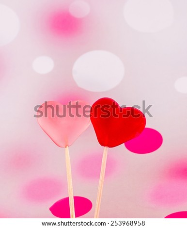 Colored (pink, red and orange), transparent heart shape jellies in wooden sticks, pink bokeh background. - stock photo