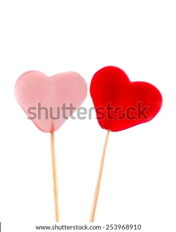 Colored (pink, red and orange), transparent heart shape jellies in wooden sticks, white background. - stock photo
