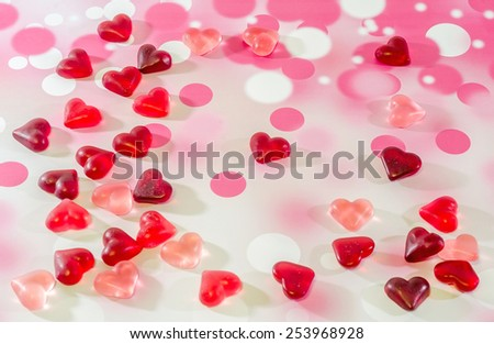 Colored (pink, red and orange), transparent heart shape jellies, pink bokeh background. - stock photo