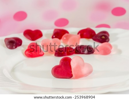 Colored (pink, red and orange), transparent heart shape jellies with ceramic plate, pink bokeh background. - stock photo