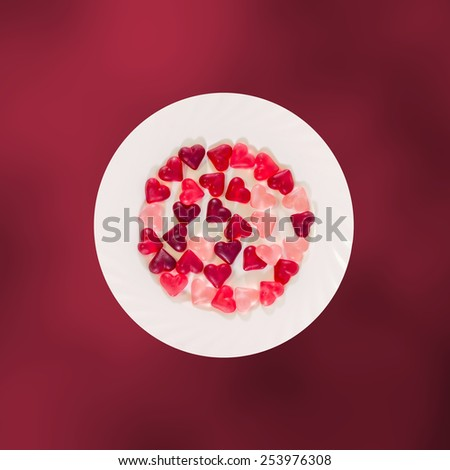 Colored (pink, red and orange), transparent heart shape jellies with ceramic plate, red degradee background, isolated. - stock photo