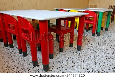 colored plastic chairs and small tables in the kindergarten class - stock photo