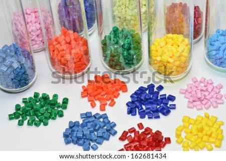 colored polymer resins in test tubes and on white table in lab - stock photo