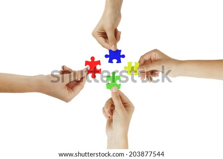 colored puzzle in hands isolated on white background - stock photo