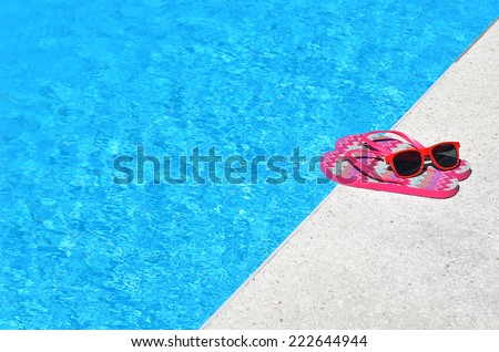 Colored sandals and sunglasses beside swimming pool -- Concept of spring break - stock photo