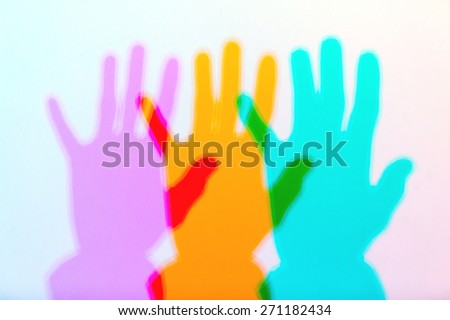 colored shadows of hand in the light spectrum with the the addition of colors effect - stock photo