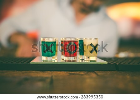 Colored shots on the bar with written letters X and O - stock photo