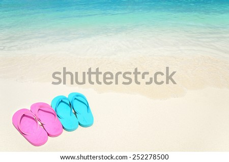 Colored slippers on the sandy beach  - stock photo