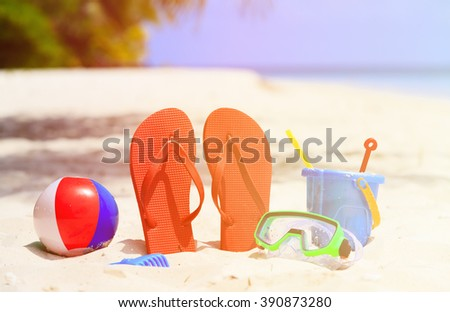 Colored slippers, toys and diving mask at beach - stock photo