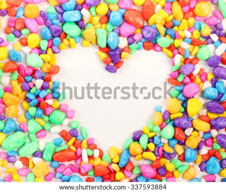 Colored stones arranged in a heart shape on white background.