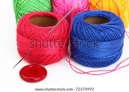 Colored thread, needles and buttons on a white background