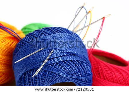Colored thread, needles  on a white background