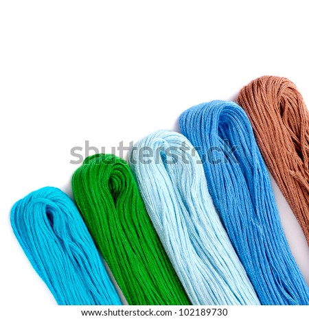 colored threads for needlework  over white, studio isolated - stock photo