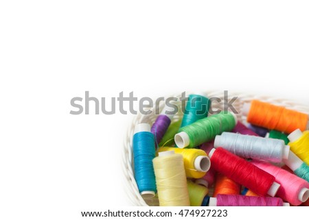 Colored threads for sewing on a white background. White basket with threads.