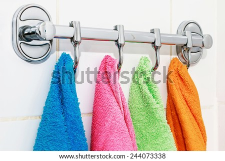 colored towels hanging on the rack in the bathroom - stock photo