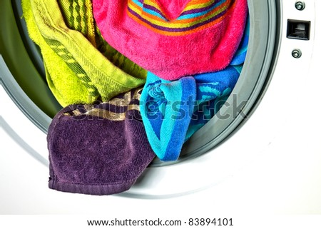 Colored towels in washing machine - stock photo
