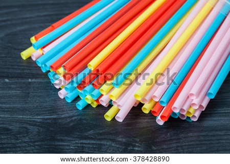 colored tubules for juice and cocktails on black wooden table - stock photo