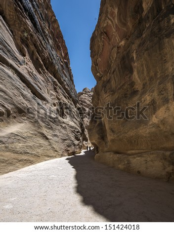 Colored walls in the canyon of the Sig (Kings Way) - narrow passage to ancient city Petra, Jordan - stock photo