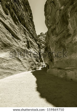 Colored walls in the canyon of the Sig (Kings Way) - narrow passage to ancient city Petra, Jordan (stylized retro) - stock photo