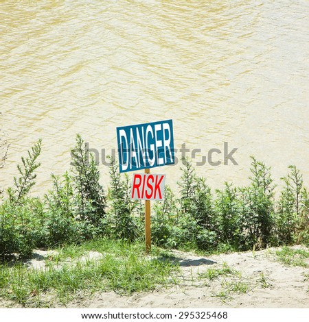 Colored warning signboard by the river - concept image