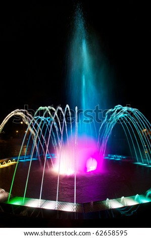Colored water fountain at night - stock photo