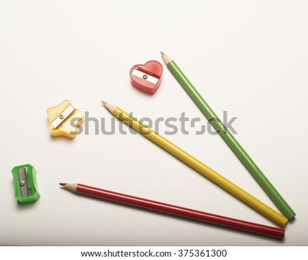 Colored writing implement/Pencils and Sharpeners/Drawing tools on a dark surface - stock photo