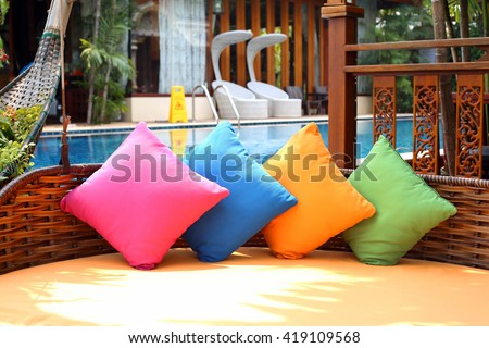 Colorfol of pillows  beside swimming pool. - stock photo