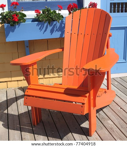 Colorful Adirondack Chair Sitting On A Patio Or Deck With A Window Box Full  Of Geraniums