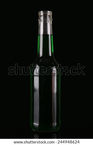 Colorful alcoholic beverages in glass bottle on dark background