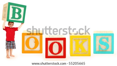 Colorful alphabet blocks spelling the word BOOKS with adorable three year old boy holding the letter B. - stock photo