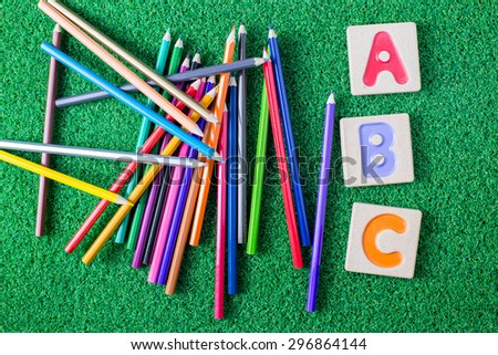 "Colorful alphabet letters ""abc"" ,and crayons on grass background - stock photo"