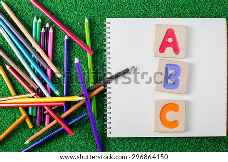 "Colorful alphabet letters ""abc"" ,crayons and the note book on grass background - stock photo"