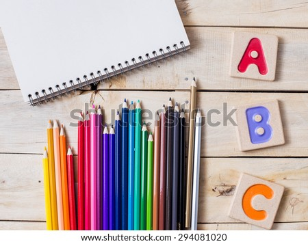 """Colorful alphabet letters """"abc"""" ,crayons and the note book on wooden background - stock photo"""