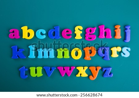 Colorful Alphabet magnetic letters on green background - stock photo