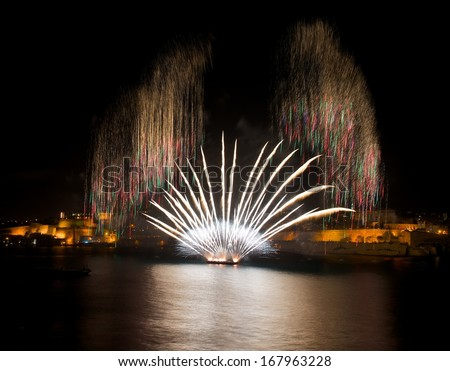 Colorful amazing fireworks in Valletta, Malta with city and reflection background, city silhouette, Malta fireworks festival, 4 of July, Independence day,explode, dark sky background and house light - stock photo