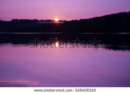 colorful and relaxing sunset over calm lake with reflection in water - stock photo