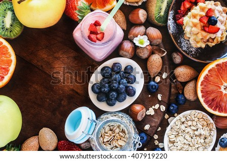 Colorful and tasty breakfast - smoothie with granola,waffles,hazelnuts, blueberries,and various fruits.Top view. - stock photo