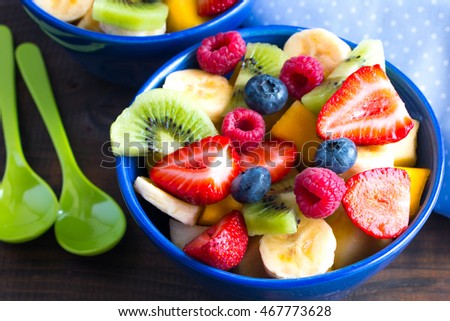 Colorful and varied fruit salad in blue bowls on rustic wooden table