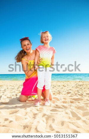 Colorful and wonderfully cheerful mood. Full length portrait of smiling trendy mother and child in colorful clothes on the seacoast