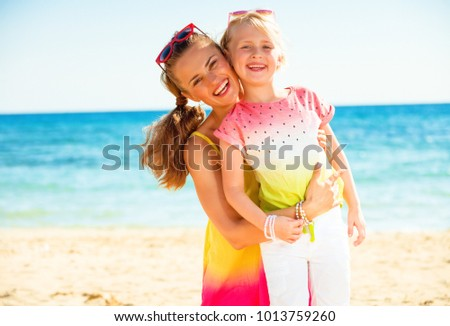 Colorful and wonderfully cheerful mood. Portrait of happy trendy mother and child in colorful clothes on the seacoast
