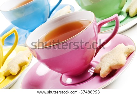 Colorful antique teacups with healthy green tea and biscuit - on a pure white background - stock photo