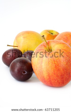 Colorful apples and plums on white background - stock photo