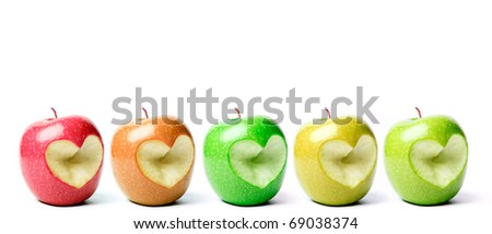 Colorful apples with cut off heart shape. - stock photo