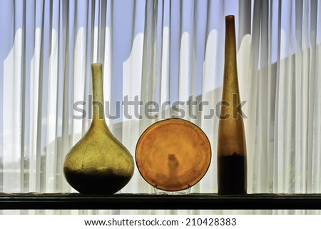 Colorful architectural bottle and plate display shot against white, translucent curtain