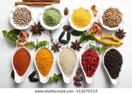 Colorful, aromatic Indian spices and herbs on a white wooden background. - stock photo