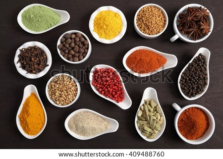 Colorful, aromatic Indian spices and herbs on a wooden background. - stock photo