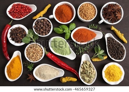 Colorful, aromatic Indian spices and herbs on a wooden background.